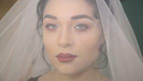 Gezicht van de jonge mooie bruid onder de witte huwelijkssluier stock videobeelden