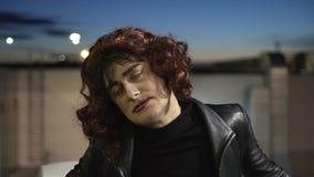 Gezicht van de mens het gekleed als vrouw, die zwarte kleren en pruik dragen, bekijkt camera stock video