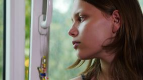 Gezicht van droevige tiener bij een venster 4k UHD stock footage