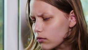 Gezicht van droevige tiener bij een venster 4k UHD stock video