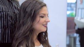 Gezicht van een glimlachend mooi meisje met samenstelling en kapsel na het werk van de stilist stock videobeelden