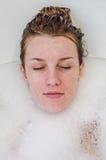 Gezicht van een jong mooi meisje in een wit bad onder zeepbels van het gel van het schuimbad, het naakt met nat haar, geniet van  Stock Afbeeldingen