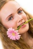 Gezicht van een meisje met roze bloem in haar mond Stock Foto