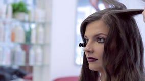 Gezicht van een mooi donkerbruin meisje dat kapsel maakt stock videobeelden