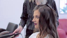 Gezicht van een mooi donkerbruin meisje terwijl haar kapper krullen maakt stock footage