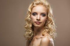 Gezicht van een mooi jong vrouwen krullend blond haar stock foto