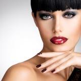 Gezicht van een vrouw met mooie donkere spijkers en sexy rode lippen Stock Afbeeldingen