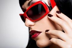 Gezicht van een vrouw in rode zonnebril met mooie donkere spijkers Stock Foto