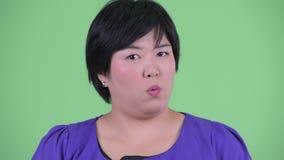 Gezicht van ernstige jonge te zware Aziatische vrouw die hoofdnr neigen stock footage