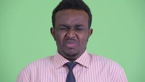 Gezicht van het beklemtoonde jonge Afrikaanse zakenman boos kijken en het schreeuwen stock footage