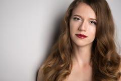Gezicht van jonge mooie donkerbruine vrouw op donkere achtergrond in rood Royalty-vrije Stock Fotografie