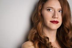 Gezicht van jonge mooie donkerbruine vrouw op donkere achtergrond in rood Stock Foto