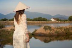 gezicht van meisje in Vietnamese hoed tegen vage achtergrond Stock Fotografie