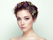 Gezicht van mooie die vrouw met bloemen wordt verfraaid stock fotografie