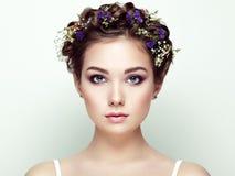 Gezicht van mooie die vrouw met bloemen wordt verfraaid stock afbeelding