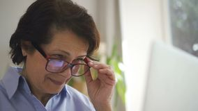 Gezicht van mooie rijpe vrouw met het bruine haar werken stock videobeelden