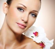 Gezicht van mooie vrouw met een witte orchideebloem Stock Foto