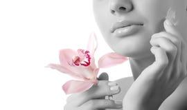 Gezicht van vrouw en orchidee stock afbeeldingen