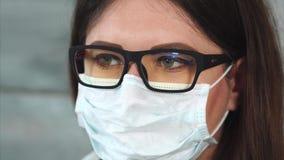 Gezicht van vrouwelijke wetenschapper of arts in wit beschermend masker Sluit omhoog mening stock footage