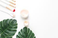 Gezichts en lichaamskuuroord gezichtsroom op de achtergrond van tropische bladeren van Monstera-palm royalty-vrije stock afbeelding