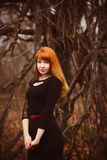 Gezichts roodharig modelmeisje in zwartekleding stock afbeeldingen