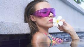 Gezichtsclose-up van sexy jonge vrouw die bikini en purpere zonnebril met witte bloem dragen die camera in de pool van het oneind stock videobeelden