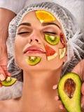 Gezichtsmasker van verse vruchten voor vrouw De schoonheidsspecialist past plakken toe Stock Foto