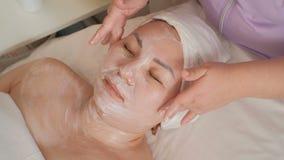 Gezichtsmassageprocedure voor een Aziatische vrouw op middelbare leeftijd Verjongend en ontspannend effect in de schoonheidssalon stock footage