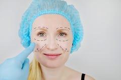 Gezichtsplastische chirurgie of facelift, facelift, gezichtscorrectie Een plastic chirurg onderzoekt een patiënt vóór plastische  stock fotografie