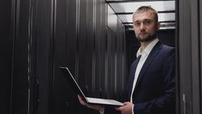 Gezichtsportret van de glimlachende mens die in serverruimte werken met laptop stock footage