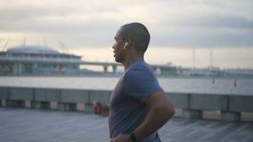Gezichtsportret van gelukkige Afrikaanse Amerikaanse volwassen professionele maniermens langzame het lopen en het luisteren muzie stock videobeelden