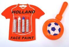 Gezichtsverf en een rammelaar in de Nederlandse nationale die kleuren voor Kingsday (Koningendag) en voor de Wereldbeker 2014, op  Stock Foto's