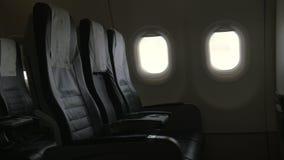 Gezien binnenlands decor van vliegtuig - zwarte leerstoelen en twee patrijspoorten stock footage