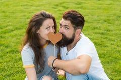 Gezien zijn hart aan haar Sensueel paar in liefde met steunhart op groen gras Sexy vrouw en gebaarde man holding stock foto's
