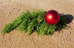 Gezierter Zweig und ein neues Jahr \ 's-Kugel auf dem Sand Lizenzfreies Stockbild