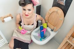 Gezinshulp die volkomen geen pret hebben bij allen die het toilet schoonmaken stock fotografie