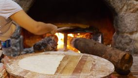 Gezleme Bread Cooked in Traditional Turkish Stove. National Food Cooking. Woman Hand Turned over Cake with Wooden Spatula. Pita in Old Stone Glowing Oven. Home stock video footage