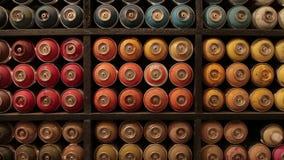 Gezoem binnen van artistiek materiaal Ladingen van gestapeld spraycans in verschillende kleuren die zich op de plank bevinden Vel stock video