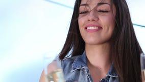 Gezoem binnen van het mooie donkerbruine vrouw roosteren met een glas champagne stock footage