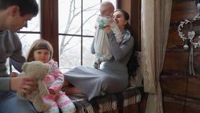 Gezoem in en controle bij de zitting van de camera gelukkige familie op de vensterbank stock footage