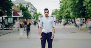 Gezoem in time tijdspanne die van Arabische student zich in straat onder stroom van mensen bevinden stock video