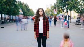 Gezoem uit tijd-tijdspanne van aantrekkelijke jonge dame die zich in voetstraat met recht gezicht bevinden en camera bekijken stock videobeelden