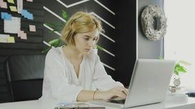 Gezoem uit Zekere onderneemster die aan laptop in haar modern bureau werken stock footage