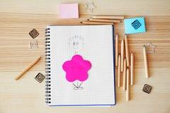 Gezogenes Bild im Notizbuch und in den bunten Bleistiften Lizenzfreie Stockbilder