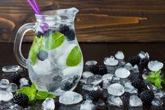 Gezond detox op smaak gebracht water met braambes en munt Koude verfrissende bessendrank met ijs op donkere houten lijst Exemplaa Stock Afbeeldingen