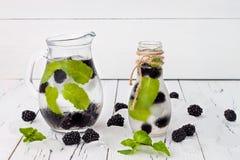 Gezond detox op smaak gebracht water met braambes en munt Koude verfrissende bessendrank met ijs op donkere houten lijst Exemplaa Stock Foto