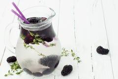 Gezond detoxwater met moerbeiboom Koude verfrissende bessendrank met ijs en thyme op witte houten lijst Het schone eten Stock Fotografie