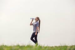 Gezond en Sportief Jong Vrouwen Drinkwater van de fles Doend Sport Openlucht stock foto's