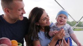 Gezond etend kind ` s, baby zijn eerste vruchten in handenmamma's eten, familie met zuigeling op weekend, ouders en kinderen die stock video