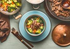 Gezond evenwichtig voedingsvoedsel met rundvleesvlees, gestoomde groenten en rijst op lijstachtergrond met plaat en bestek, hoogs stock afbeeldingen